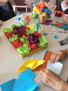 Table d'atelier avec tous les lotus en serviette pliés par les personnes âgées