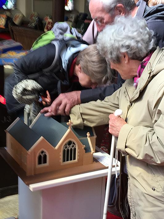 plusieurs personnes découvrent la maquette de l'église. Maquette réalisée par Architact