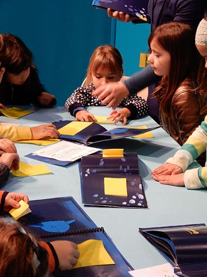 Salon FOUGERE enfants manipulant le livre et pliant après la lecture contée
