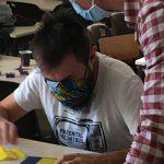 Afin de créer une action éducative utilsant l'origami, les étudiants ont imaginé des actions et les ont tester auprès de leurs collègues. ici nous voyons un éducateur aidant une personne déficiente visuelle.