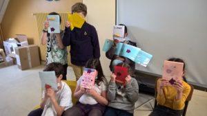 Un groupe d'enfant présentent leur carnet fabriquer pendant la séance accompagner de Petite feuille en forme de poisson