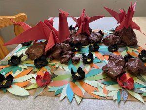 Trois dragons en origami disposés sur un support décoré de nénuphars en papier