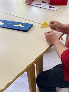 Adulte manipulant un bateau en origami à l'aide du carnet de la mallette OSA