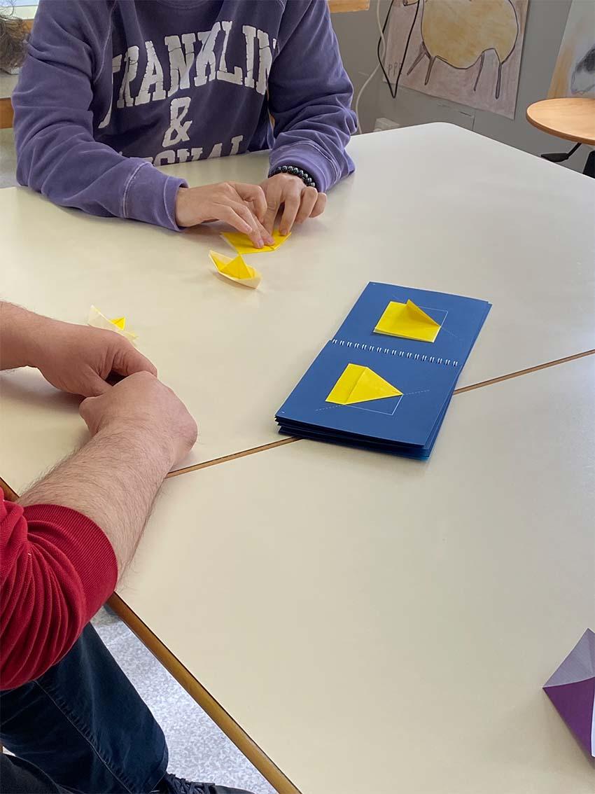 Deux adultes manipulant un bateau en origami, avec l'aide du. carnet de la mallette OSA